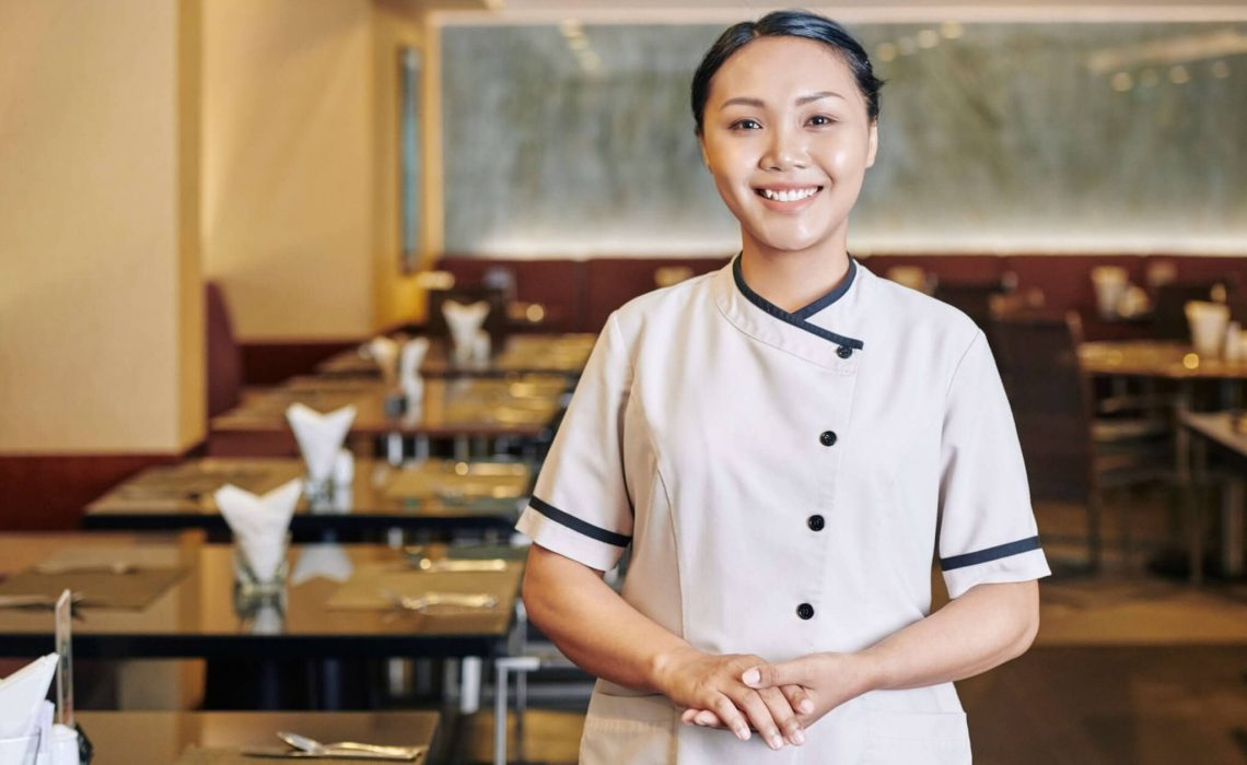 Portrait of young Asian waitress in uniform smiling at camera while standing at the empty restaurant