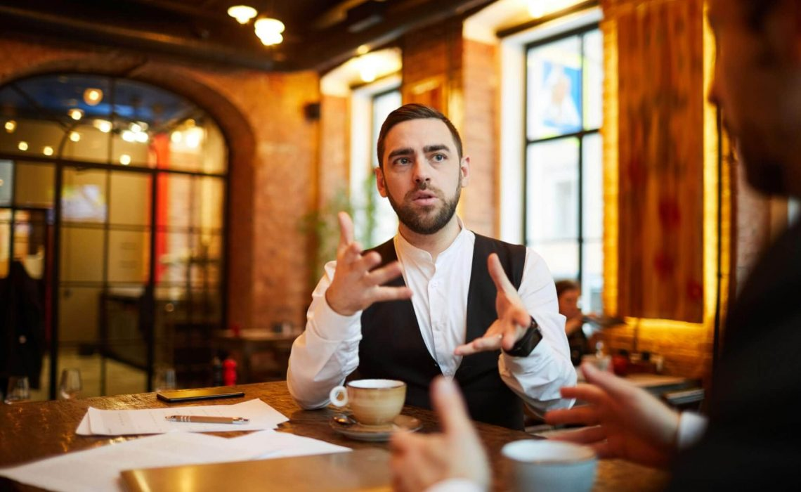 Portrait of successful businessman talking to partner during meeting in cafe and gesturing actively, copy space