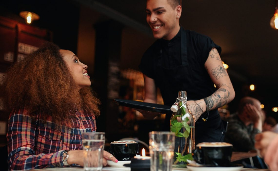 Woman talking to waiter at restaurant. Young woman sitting at cafe with waiter standing by smiling.